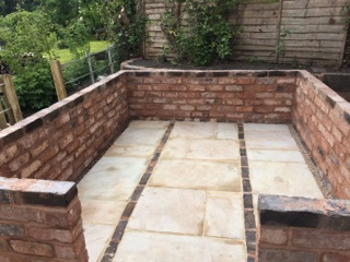 an image of a reclaimed brick greenhouse base from the front